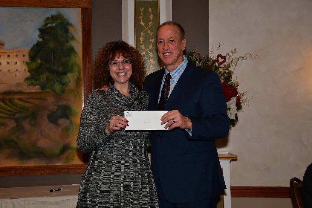 TIES Coordinator Marcy Hagen accepts the Community Grant check from Buffalo Bills legend and philanthropist Jim Kelly