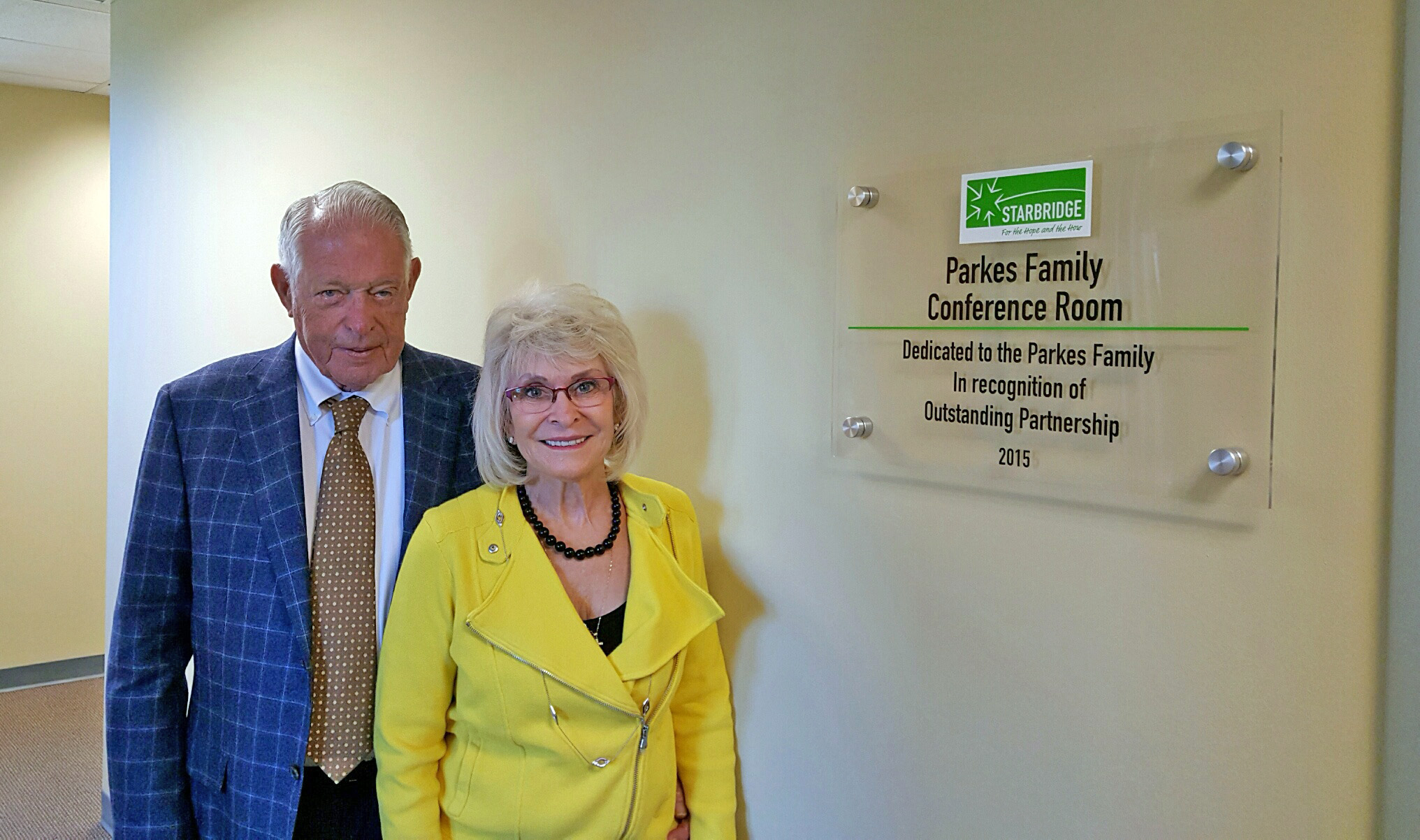 Walter and Barbara Parkes outside the Parkes Family Conference Room at Starbridge's main office