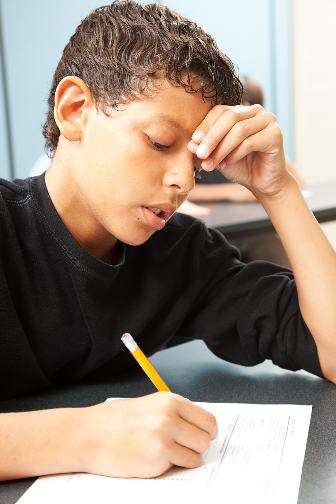 Stock photo showing school aged boy writing on school work and holding head with one hand