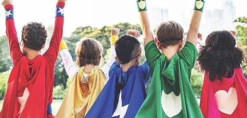 Photo of five kids from the back in brightly colored superhero capes